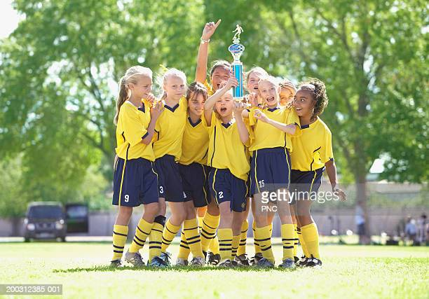 Girls (10-17) in soccer uniforms holding trophy on field, cheering