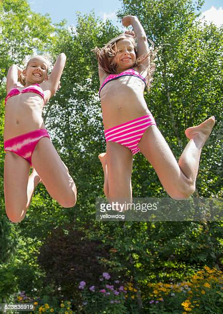 girls in swimming costume jumping in garden - preadolescente fotografías e imágenes de stock
