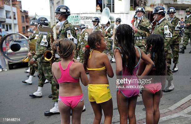 Girls in swimwear watch the military band parading during the celebrations for the anniversary of the independence of Colombia in 13 Commune...