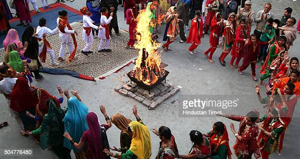 Girls in traditional attire dance around a bonfire as they celebrate Lohri festival on January 13, 2016 in Jammu, India. Lohri celebrates the harvest...