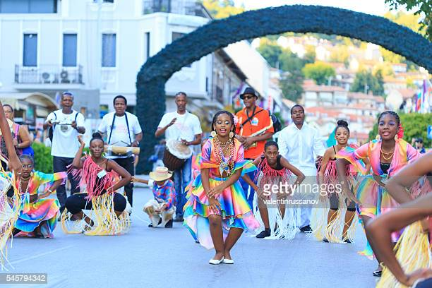 Girls in traditional costumes dancing in front of musicians