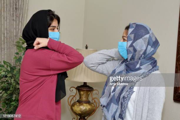 girls in veil (hijab) doing social greetings with elbows to protect themselves from coronavirus (covid-19). - pakistan stock pictures, royalty-free photos & images