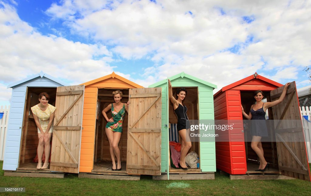 Girls in vintage bikinis pose for a photograph in the driver's enclosure during Goodwood Revival 2010 at Goodwood on September 17, 2010 in Chichester, England. The event is based around a classic car race meeting and airshow but celebrates all things 1945 until 1966.