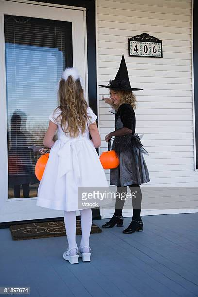 Girls in wtich and princess Halloween costumes trick or treating
