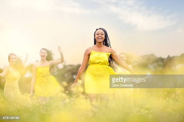 Girls in yellow dancing on meadow