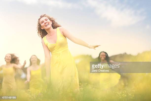 girls in yellow dancing on meadow - long bright yellow dress stock pictures, royalty-free photos & images