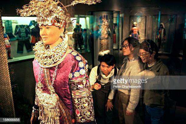 Girls inspect a traditional embroidered silk costume in the Shanghai Museum of Art..