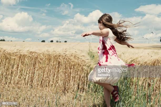 Mädchen tanzt vor der Getreide-Feld und Windturbinen