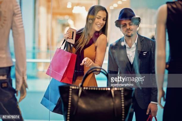 女の子は店の窓で彼氏にバッグを見せています。 - 欲望 ストックフォトと画像