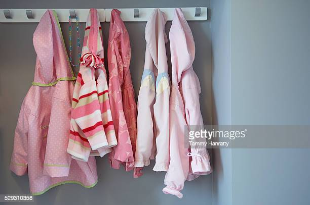 Girl's jackets and coats hanging on pegs