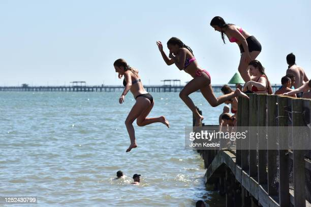 Girls jump from a jetty into the sea as crowds of people gather on the beach on June 25, 2020 in Southend-on-Sea, England. The UK is experiencing a...