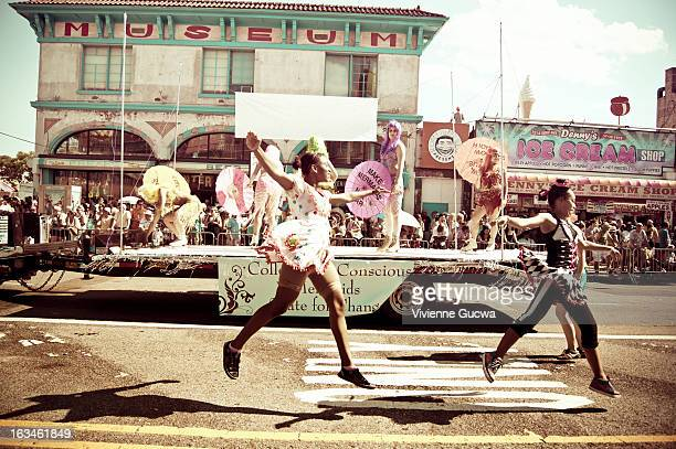 Girls jump in the air in front of a parade float at the Coney Island Annual Mermaid Parade held in Brooklyn, New York City. The Coney Island Museum...