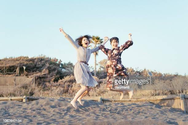 jeunes filles sautant à la plage. - vacances à la mer photos et images de collection
