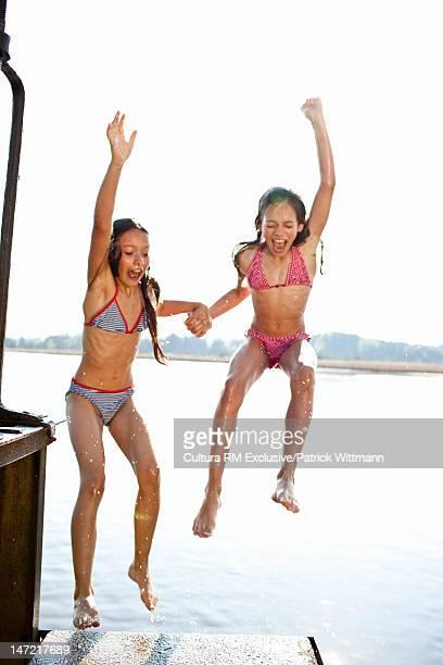 Girls jumping backwards into lake