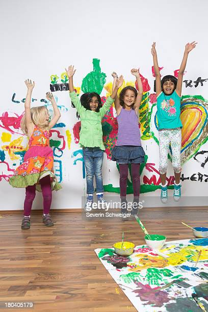 Girls jumping in front of painted wall