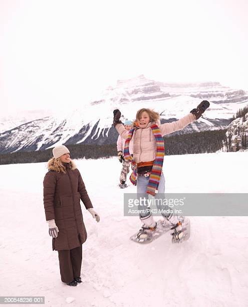 Girls (10-11) jumping in snow, woman looking at her