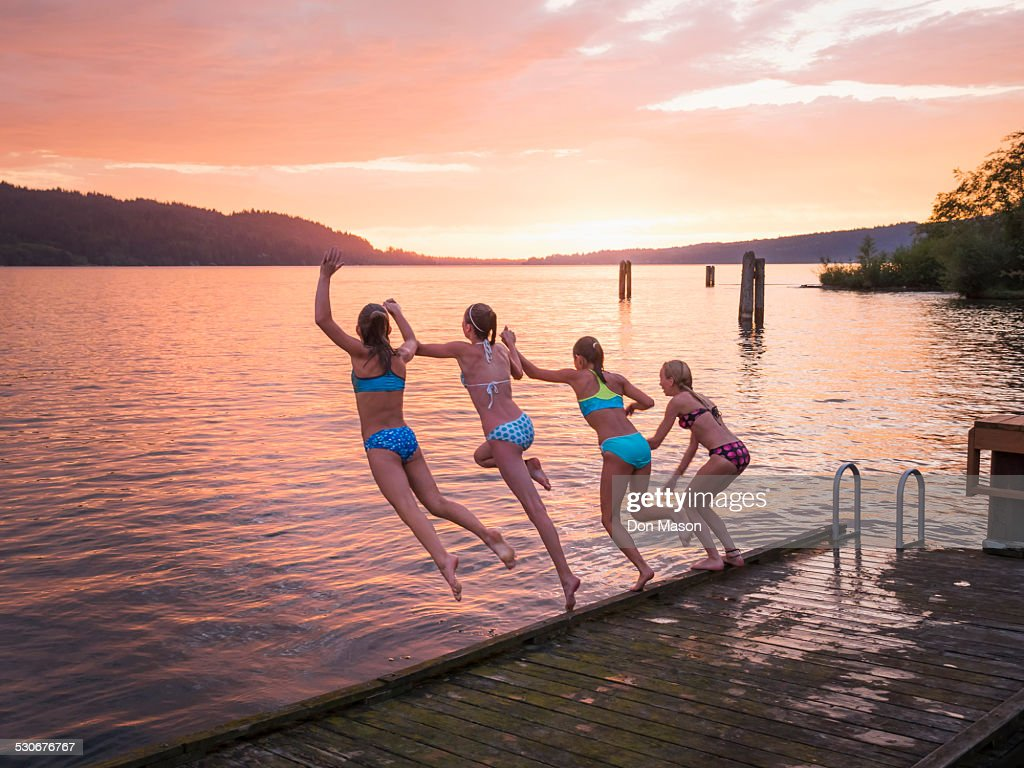 Girls jumping into lake from wooden dock : Stock Photo