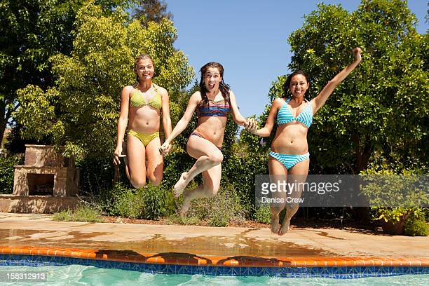 Girls jumping into swimming pool together