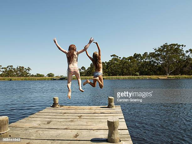 2 girls jumping of a jetty