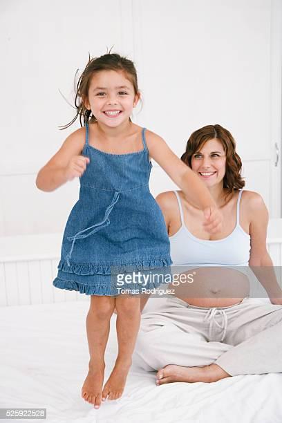 girls jumping on bed - ドロストパンツ ストックフォトと画像