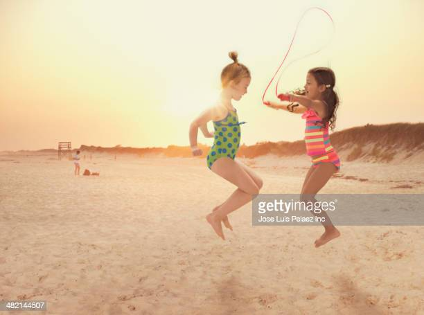 Girls jumping rope on beach