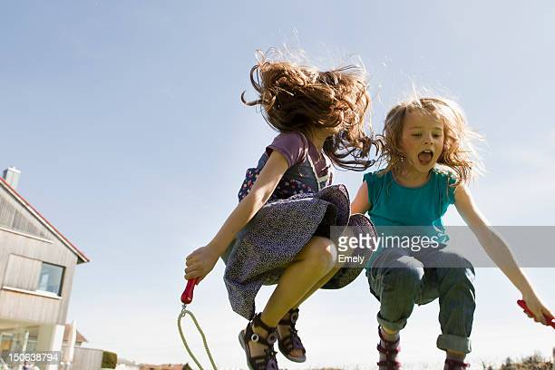 Girls jumping rope together outdoors