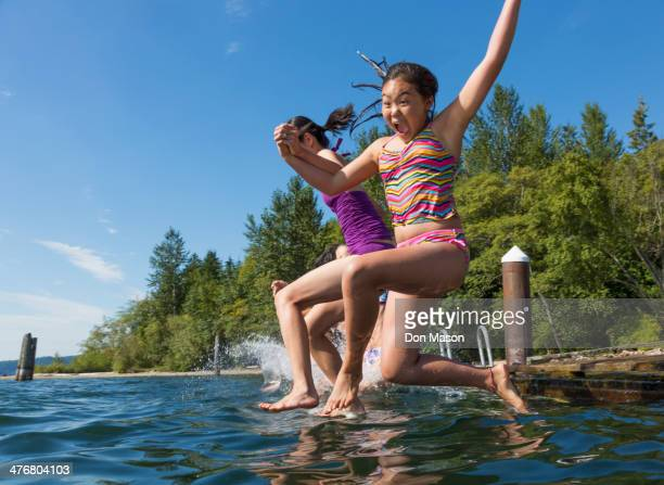 Girls jumping together into lake