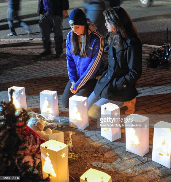 Girls kneel during candle light vigil following shooting at Sandy Hook Elementary school where Adam Lanza opened fire inside school killing 27...