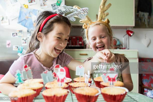 Girls laugh whilst decorating Christmas cupcakes