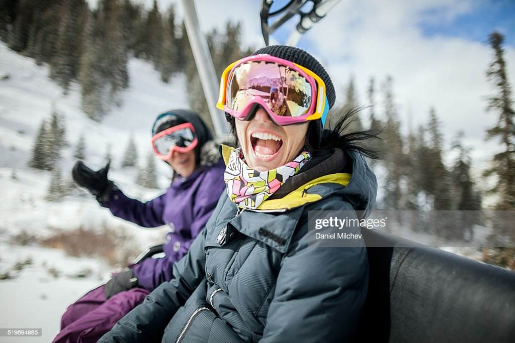 Girls laughing and having fun on a chair lift. : Stock Photo