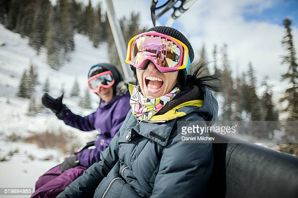 girls laughing and having fun on a chair lift. - ski lift stock pictures, royalty-free photos & images