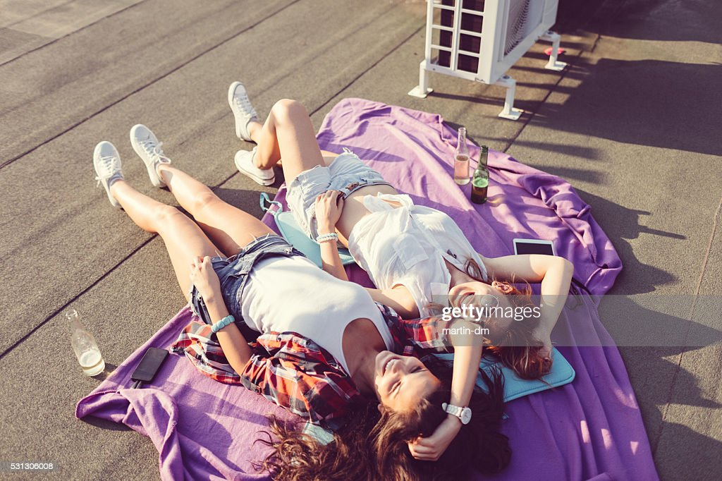 Girls laughing and sunbathing on the rooftop : Stock Photo
