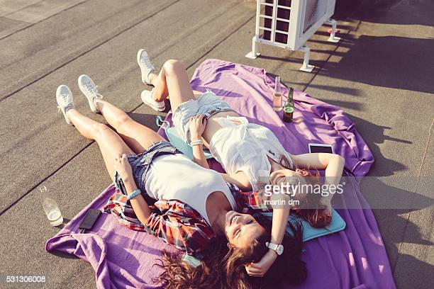 girls laughing and sunbathing on the rooftop - girls sunbathing stock pictures, royalty-free photos & images