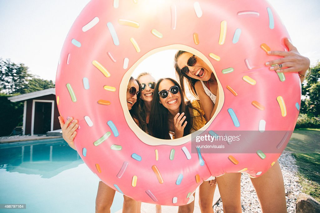 Girls laughing while holding a pool inflatable like a frame : Stock Photo