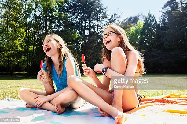 girls laughing with ice lolly - swimwear stock photos and pictures