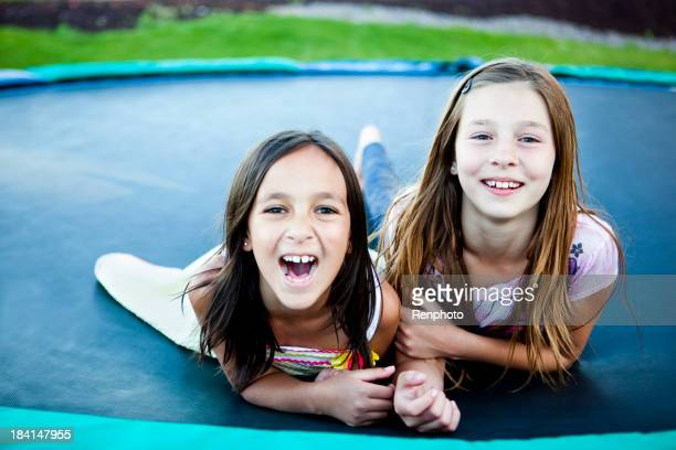 Mädchen Leg dich auf Trampolin
