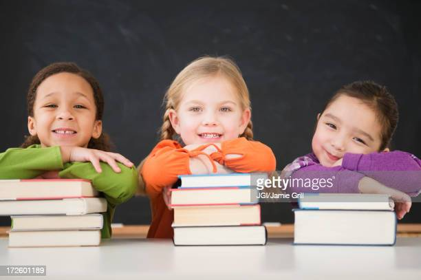 Girls leaning on stacks of books in classroom