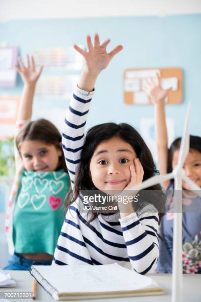 Girls learning about windmills raising hands in classroom