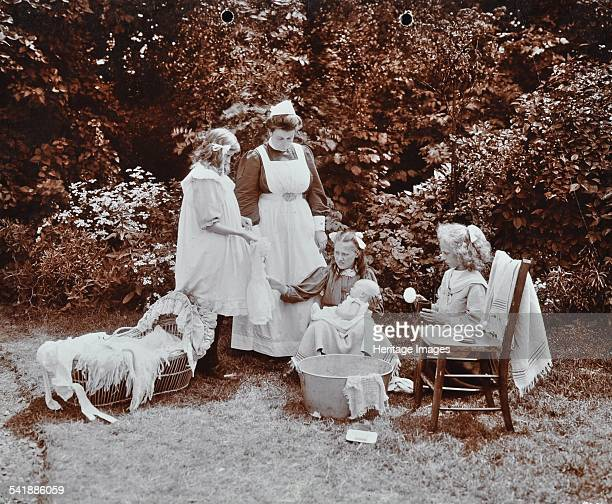 Girls learning infant care, Birley House Open Air School, Forest Hill, London, 1908. Three girls, being supervised by a nurse, bathing and dressing a...