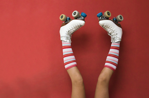 Girl's legs wearing long socks and rollerskates upside down against a wall - gettyimageskorea