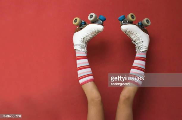 girl's legs wearing long socks and rollerskates upside down against a wall - patinar - fotografias e filmes do acervo