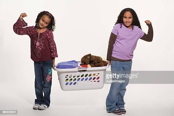 Girls lifting laundry basket