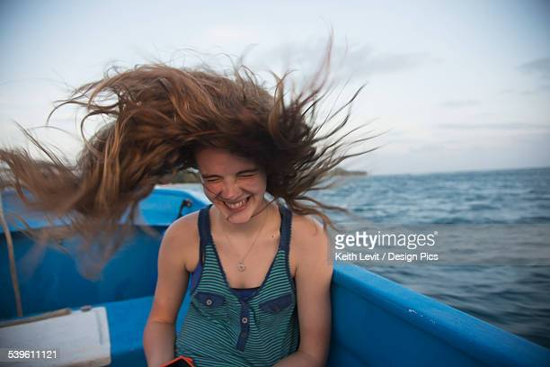 A Girls Long Hair Whipping Through The Air On A Boat Ride