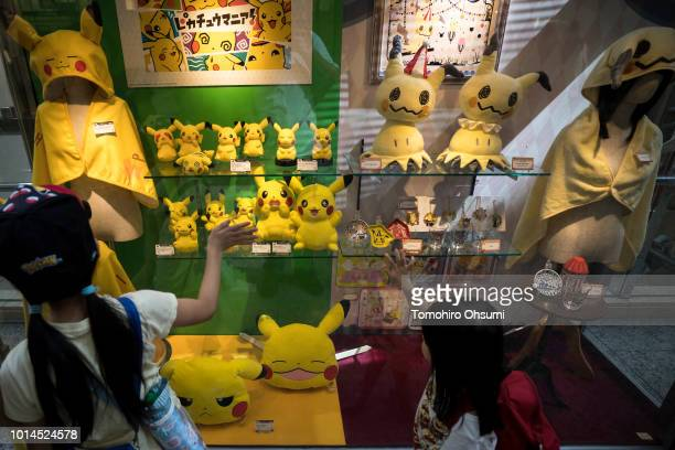Girls look at plush toys of Pikachu a character from Pokemon series game titles at a shopping mall during the Pikachu Outbreak event hosted by The...
