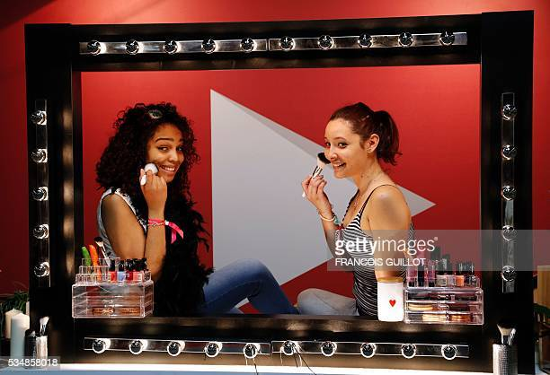 Girls look in a mirror as they put make up during the Get Beauty fair a beauty and fashion fair inspired by the US 'Beautycon' event gathering of...