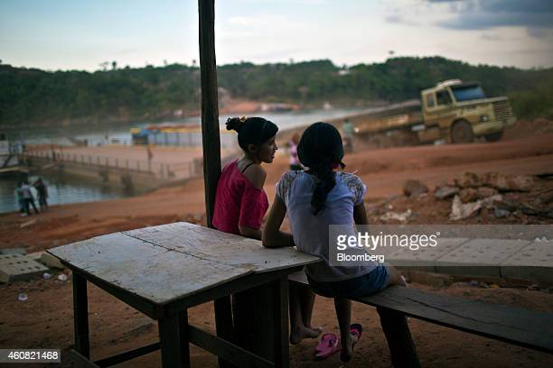 Girls look on as a logging truck disembarks from a ferry on the BR 263 road between Altamira and Anapu in the southern part of Amazonian state of...