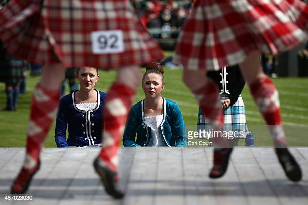 Girls look on at dancers as they wait to compete in the Highland Dancing competition at the Braemar Gathering on September 5 2015 in Braemar Scotland...