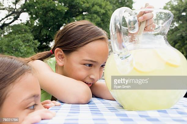 Girls looking at a pitcher of lemonade