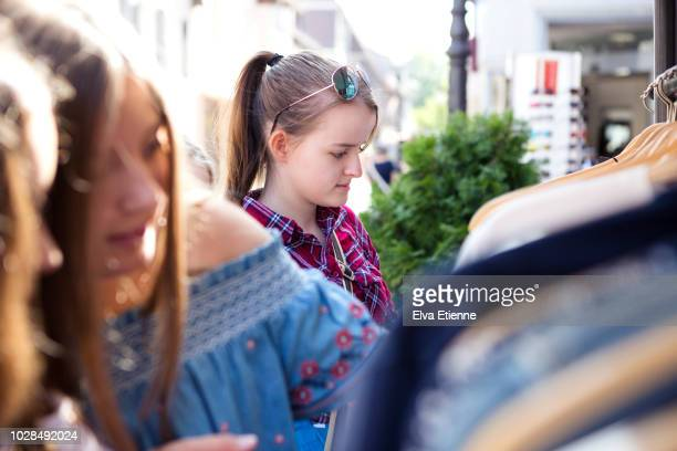 girls looking at clothes on a rack outside a shop in germany - mädchen 14 jahre stock-fotos und bilder