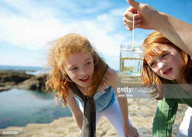 2 girls looking at fish in jar by sea